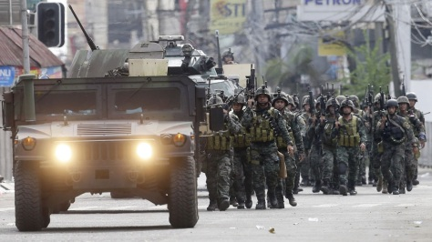 Soldiers of the Light Reaction Battallion march behind a Humvee. Photo courtesy of Associated Press / Bullit Marquez