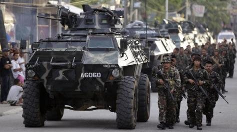 Soldiers march alongside Simba vehicles. Photo courtesy of Associated Press / Bullit Marquez